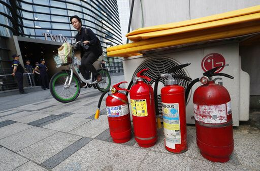 Fire extinguishers are placed near a building where the Japanese embassy is located in Seoul, South Korea, Friday, July 19, 2019. South Korean police say a man has set himself on fire in front of the Japanese Embassy in Seoul amid rising trade disputes between Seoul and Tokyo.