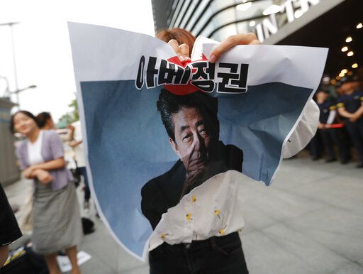 "In this Thursday, July 18, 2019, photo, a protester tries to tear a paper showing an image of Japanese Prime Minister Shinzo Abe during a rally denouncing the Japanese government's decision on their exports to South Korea in front of the Japanese embassy in Seoul, South Korea. South Korean police on Friday, July 19, say a man has set himself on fire in front of the Japanese Embassy in Seoul amid rising trade disputes between Seoul and Tokyo. The signs read ""Abe's government."""