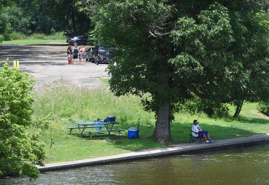 A fisherman sits in the shade while others gather in the sun near the Voyaguer Landing Forest Preserve boat launch on the Fox River in Elgin Saturday.