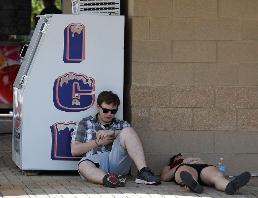 Aaron Repa, 18, of Algonquin and Brea Kanak, 18, of West Chicago try to keep cool in the shade next to an ICE machine as temperatures reached in the mid-90s Saturday at the Kane County Fair.