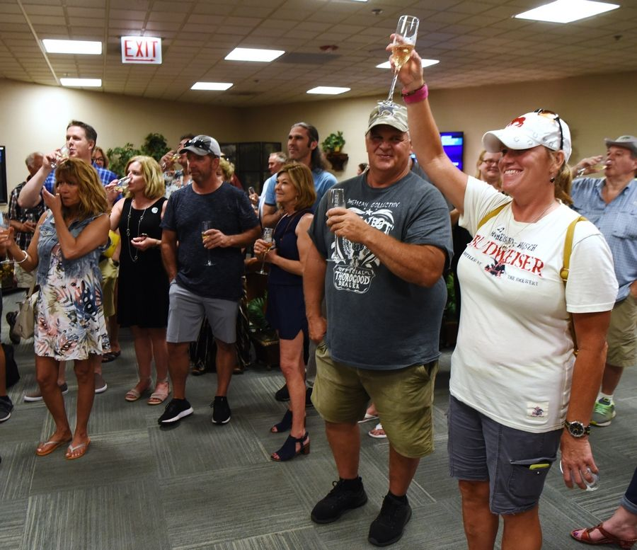 Friends and family members have a toast following the running of the Mike Spellman Memorial Handicap, held in honor of the late Daily Herald sports winter, at Arlington International Racecourse Saturday.