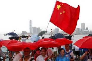 Pro-China supporters hold red umbrellas and a Chinese national flag during a counter-rally in support of the police in Hong Kong Saturday, July 20, 2019. Police in Hong Kong have raided a homemade-explosives manufacturing lab ahead of another weekend of protests in the semi-autonomous Chinese territory.(AP Photo/Vincent Yu)