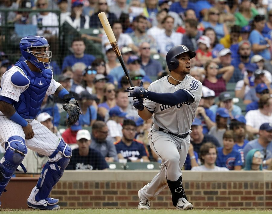 San Diego Padres' Francisco Mejia, right, watches his solo home run during the seventh inning of a baseball game against the Chicago Cubs in Chicago, Sunday, July 21, 2019.
