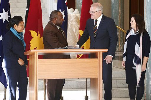 Papua New Guinea's Prime Minister James Marape, second from left, shakes hands with Australian Prime Minister Scott Morrison, watched by their respective wives Rachael Marape, left, and Jenny Morrison after signing the visitors' book at Australia's Parliament House in Canberra Monday, July 22, 2019. Marape says his country's relationship with China in not open to discussion during his current visit to Australia.