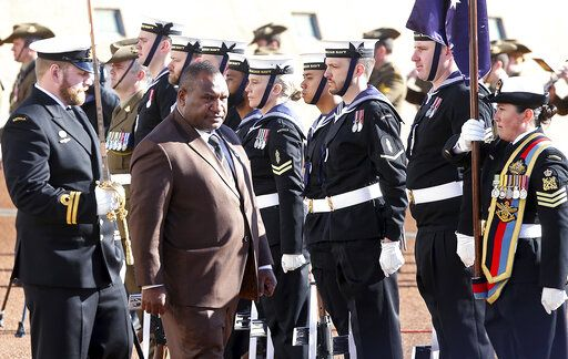 Papua New Guinea Prime Minister James Marape, second from left, inspects troops as he is officially welcomed to Australia's Parliament House in Canberra Monday, July 22, 2019. Marape says his country's relationship with China in not open to discussion during his current visit to Australia.