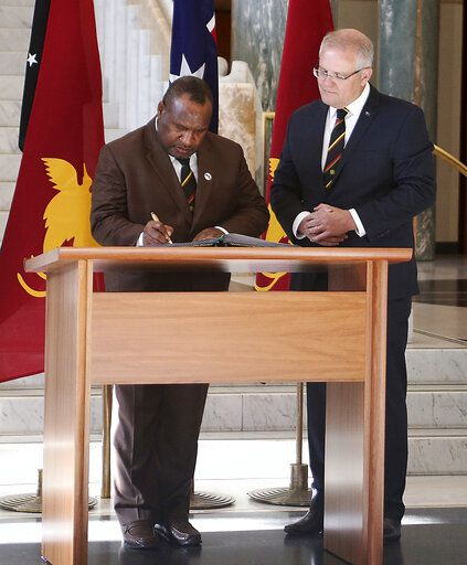 Papua New Guinea's Prime Minister James Marape, left, signs the visitors' book at Australia's Parliament House in Canberra watched by Australian Prime Minister Scott Morrison Monday, July 22, 2019. Marape says his country's relationship with China in not open to discussion during his current visit to Australia.