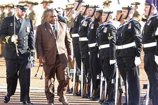 Papua New Guinea's Prime Minister James Marape, second from left, inspects troops as he is officially welcomed to Australia's Parliament House in Canberra Monday, July 22, 2019. Marape says his country's relationship with China in not open to discussion during his current visit to Australia.