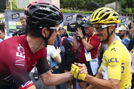 France's Julian Alaphilippe wearing the overall leader's yellow jersey shakes hands with Britain's Geraint Thomas as they arrive at the start of the fifteenth stage of the Tour de France cycling race over 185 kilometers (114,95 miles) with start in Limoux and finish in Prat d'Albis, France, Sunday, July 21, 2019.