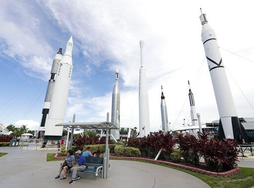 Guests relax in the rocket garden at the Kennedy Space Center Visitor Complex during the Apollo 11 anniversary, Saturday, July 20, 2019, in Cape Canaveral, Fla.