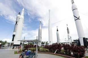 Guests relax in the rocket garden at the Kennedy Space Center Visitor Complex during the Apollo 11 anniversary, Saturday, July 20, 2019, in Cape Canaveral, Fla. (AP Photo/John Raoux)