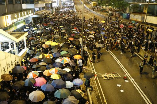 Protesters move along a street in Hong Kong on Sunday, July 21, 2019. Protesters in Hong Kong pressed on Sunday past the designated end point for a march in which tens of thousands repeated demands for direct elections in the Chinese territory and an independent investigation into police tactics used in previous demonstrations.