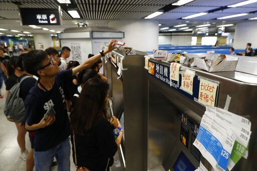 Commuters leave spare change and train tickets for protesters to use at a subway station in Hong Kong, Sunday, July 21, 2019. Protesters in Hong Kong pressed on Sunday past the designated end point for a march in which tens of thousands repeated demands for direct elections in the Chinese territory and an independent investigation into police tactics used in previous demonstrations.