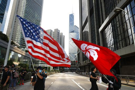 Protesters wave the Hong Kong and United States flag during a march in Hong Kong on Sunday, July 21, 2019. Tens of thousands of Hong Kong protesters marched from a public park to call for an independent investigation into police tactics.
