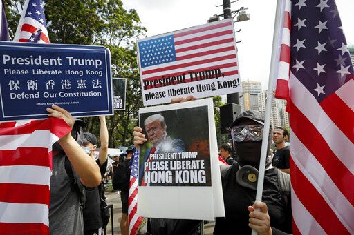Protesters hold a placard featuring U.S. President Donald Trump and U.S. flags as they take part in a march at Victoria Park in Hong Kong, Sunday, July 21, 2019. Thousands of Hong Kong protesters marched from a public park to call for an independent investigation into police tactics.