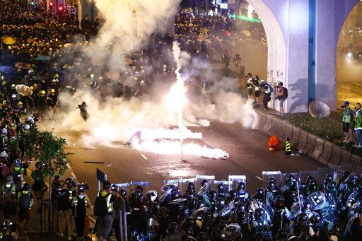 Protesters are engulfed by teargas during a confrontation with riot police in Hong Kong Sunday, July 21, 2019. Hong Kong police launched tear gas at protesters Sunday after a massive pro-democracy march continued late into the evening. The action was the latest confrontation between police and demonstrators who have taken to the streets to protest an extradition bill and call for electoral reforms in the Chinese territory. (Lo Kwanho/HK01 via AP)