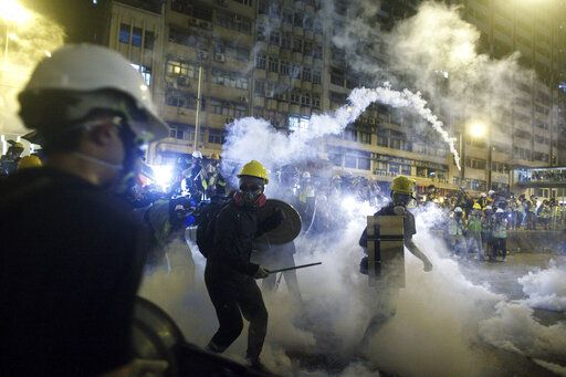 Protesters react to tear gas during a confrontation with riot police in Hong Kong Sunday, July 21, 2019. Hong Kong police launched tear gas at protesters Sunday after a massive pro-democracy march continued late into the evening. The action was the latest confrontation between police and demonstrators who have taken to the streets to protest an extradition bill and call for electoral reforms in the Chinese territory. (Eric Tsang/HK01 via AP)