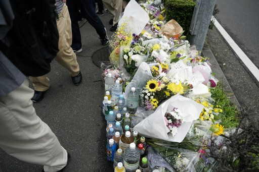 Pedestrians walk past a makeshift memorial set up to honor the victims of Thursday's fire at the Kyoto Animation Studio building, Saturday, July 20, 2019, in Kyoto, Japan. The man suspected of setting ablaze a beloved Japanese animation studio was raging about theft and witnesses and media reported he had a grudge against the company, as questions arose why such mass killings keep happening in the country.