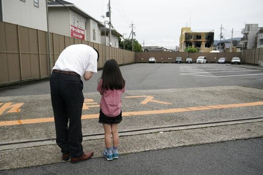 A man and his daughter pray for the victims of Thursday's fire at the Kyoto Animation Studio building, background right, Saturday, July 20, 2019, in Kyoto, Japan. The man suspected of setting ablaze a beloved Japanese animation studio was raging about theft and witnesses and media reported he had a grudge against the company, as questions arose why such mass killings keep happening in the country.