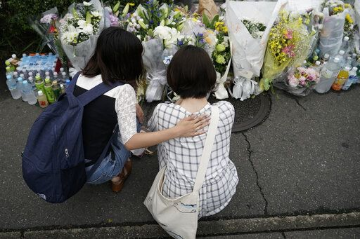 Two women pay their respects at a makeshift memorial to honor the victims of Thursday's fire at the Kyoto Animation Studio building, Saturday, July 20, 2019, in Kyoto, Japan. The man suspected of setting ablaze a beloved Japanese animation studio was raging about theft and witnesses and media reported he had a grudge against the company, as questions arose why such mass killings keep happening in the country.