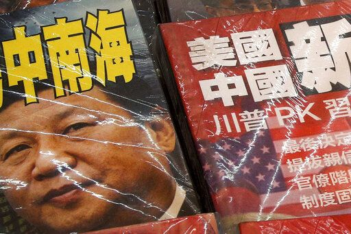 In this July 4, 2019, photo, magazines with front covers featuring Chinese President Xi Jinping with South China Sea and Xi against U.S. President Donald Trump are placed on sale at a roadside bookstand in Hong Kong. The United States said it's concerned by reports of China's interference with oil and gas activities in the disputed waters of the South China Sea, where Vietnam accuses Beijing of violating its sovereignty.