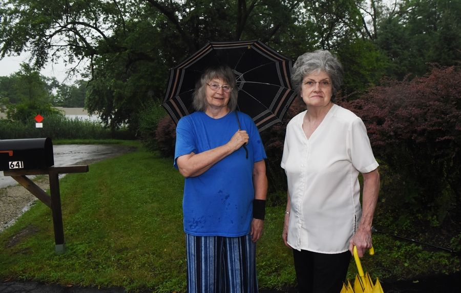 Debra Noble, left, and Joyce Winke stand at the bottom of Winke's driveway at the end of their cul-de-sac. Residents who live just west of I-355 between North Avenue and St. Charles Road near Lombard have sought a noise wall for three decades.
