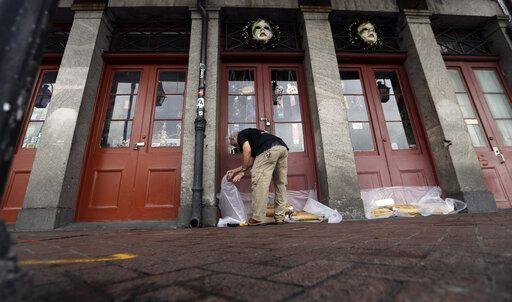 FILE - In this July 12, 2019, file photo Jake Summers puts concrete bags in front of a business in the French Quarter in New Orleans, ahead of Tropical Storm Barry. With earthquakes in California and Hurricane Barry striking states along the Gulf of Mexico and in the Midwest, small business owners should look at their insurance policies and determine how well covered they'd be in the event of a natural disaster.