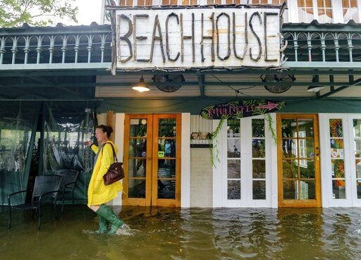 FILE - In this July 13, 2019, file photo Aimee Cutter, the owner of Beach House restaurant, walks through water surge from Lake Pontchartrain on Lakeshore Drive in Mandeville, La., ahead of Tropical Storm Barry. With earthquakes in California and Hurricane Barry striking states along the Gulf of Mexico and in the Midwest, small business owners should look at their insurance policies and determine how well covered they'd be in the event of a natural disaster.