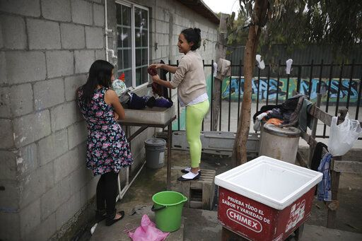 In this June 06, 2019 photo, Salvadoran teen migrant Milagro de Jesus Henriquez Ayala chats with a friend while she washes her clothes at Agape World Mission shelter, in Tijuana, Mexico. About 25 people sleep in the cinderblock room crammed with seven bunkbeds at a Tijuana shelter overflowing with migrants, primarily from Honduras, Guatemala and El Salvador but also from as far away as Africa.