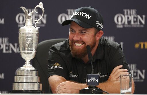 Ireland's Shane Lowry smiles as he sits next to the Claret Jug trophy while he attends a press conference after he won the British Open Golf Championships at Royal Portrush in Northern Ireland, Sunday, July 21, 2019.
