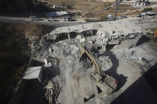 Israeli forces destroy a building in a Palestinian village of Sur Baher, east Jerusalem, Monday, July 22, 2019. Israeli work crews have begun demolishing dozens of Palestinian homes in an east Jerusalem neighborhood. Monday's demolitions cap a years-long legal battle over the buildings, which straddle the city and the occupied West Bank.
