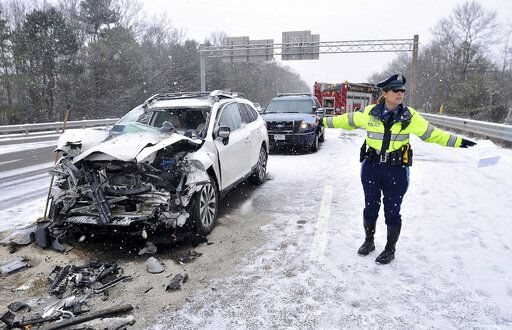 FILE- In this Jan. 31, 2017, file photo, a Massachusetts state trooper stands near a SUV that slammed into the rear of a dumpster truck causing a chain reaction collision in Plainville, Mass. An Associated Press survey shows that Massachusetts is one of only five states where the primary state law enforcement agency is not equipped with dashboard cameras. (Mark Stockwell/The Sun Chronicle via AP, File)