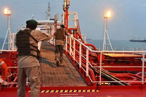 In this Sunday, July 21, 2019 photo, two armed members of Iran's Revolutionary Guard inspect the British-flagged oil tanker Stena Impero, which was seized in the Strait of Hormuz on Friday by the Guard, in the Iranian port of Bandar Abbas. Global stock markets were subdued Monday while the price of oil climbed as tensions in the Persian Gulf escalated after Iran's seizure of a British oil tanker on Friday. (Morteza Akhoondi/Mehr News Agency via AP)