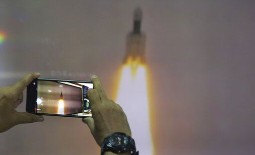 A man at New Delhi's Nehru Planetarium, takes pictures of a web cast of the lift off of Indian Space Research Organization (ISRO)'s Geosynchronous Satellite launch Vehicle (GSLV) MkIII carrying Chandrayaan-2 from Satish Dhawan Space center in Sriharikota, India, Monday, July 22, 2019. India's space agency says it has launched an unmanned spacecraft to the far side of the moon a week after aborting the mission due to a technical problem.
