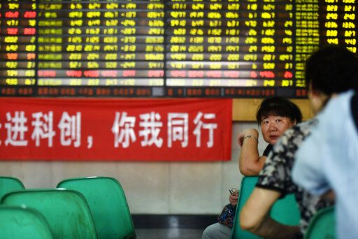 Stock investors chat beside a banner promoting the newly launched STAR market in a brokerage house in Hangzhou in east China's Zhejiang province Monday, July 22, 2019, the trading day of the new board. (Chinatopix via AP)