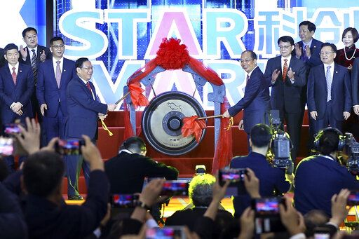 Li Qiang, center left, Shanghai's Party chief, and Yi Huiman, center right, chairman at China Securities Regulatory Commission, strikes a gong to launch the SSE STAR Market in the hall of Shanghai Securities Exchange in Shanghai, China, Monday, July 22, 2019. Trading started Monday on a Chinese stock market for high-tech companies that play a key role in official development plans that are straining relations with Washington. (Chinatopix via AP)