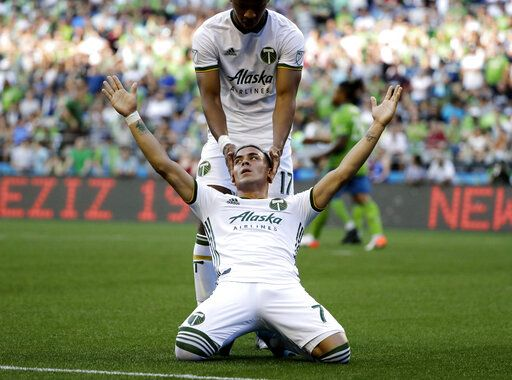 Portland Timbers forward Brian Fernandez, front, celebrates with Jeremy Ebobisse, top, after Fernandez scored a goal against the Seattle Sounders during the first half of an MLS soccer match, Sunday, July 21, 2019, in Seattle.