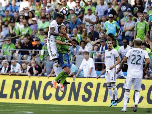 Portland Timbers defender Julio Cascante, left, heads the ball above Seattle Sounders forward Nicolas Lodeiro during the first half of an MLS soccer match, Sunday, July 21, 2019, in Seattle.