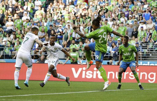 Portland Timbers forward Brian Fernandez, left, kicks a goal as forward Jeremy Ebobisse, second from left, as Seattle Sounders' defenders Roman Torres (29) and Kelvin Leerdam, right, look on during the first half of an MLS soccer match, Sunday, July 21, 2019, in Seattle.