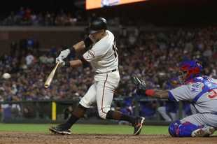 San Francisco Giants' Joe Panik, left, hits an RBI-double in front of Chicago Cubs catcher Martin Maldonado during the eighth inning of a baseball game in San Francisco, Monday, July 22, 2019. (AP Photo/Jeff Chiu)