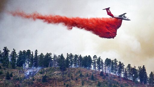 In this Monday, July 22, 2019, photo, an air tanker drops retardant on a ridge overlooking the North Peak neighborhood as the Museum Fire burns north of Flagstaff, Ariz. At least 1000 acres have burned and the fire continues to grow as crews were trying to keep the wildfire in a popular Arizona vacation area from homes and a ski resort. (Tom Tingle/The Arizona Republic via AP)