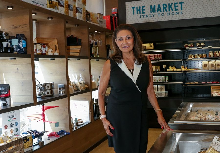 Mae Calamos, owner of Che Figata in Naperville, shows some of the many Italian delicacies in the restaurant's market.