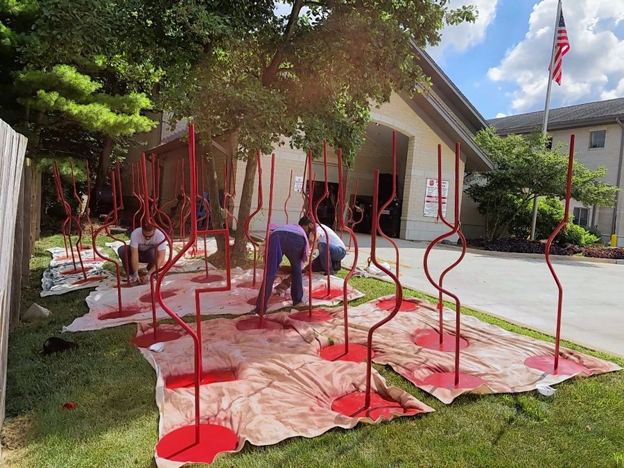 Caterpillar volunteers paint red kettles and stands for The Salvation Army outside of the Tri-Cities site in St. Charles
