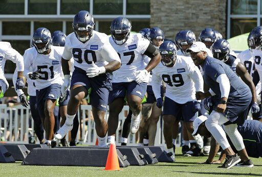 Seattle Seahawks defensive tackle Jarran Reed (90) runs a drill with teammates during NFL football training camp, Thursday, July 25, 2019, in Renton, Wash.