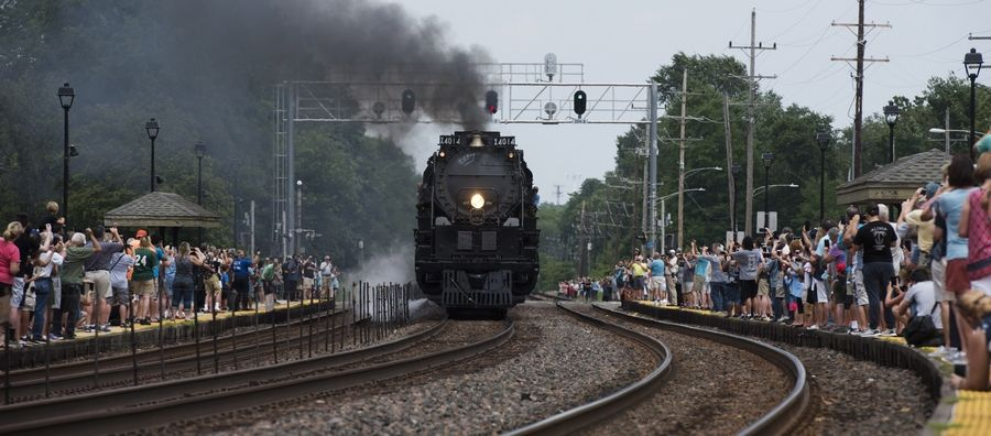 People line both sides of the tracks to take photos as the Union Pacific Big Boy steam locomotive 4014 approaches downtown Glen Ellyn.
