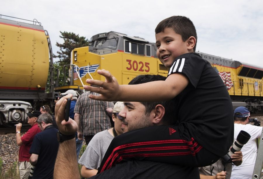 Mikey Lopes, 5, and his uncle, Jesse Flores, both of Des Plaines, watch as the train led by Union Pacific Big Boy steam locomotive 4014 and a trailing diesel unit passes through Des Plaines.