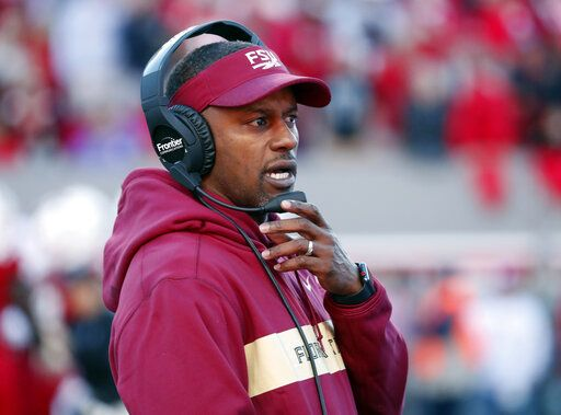 "FILE - In this Saturday, Nov. 3, 2018 file photo, Florida State head coach Willie Taggart confers on his headset during the first half of an NCAA college football game against North Carolina State in Raleigh, N.C.  James Blackman has the confidence of a starting quarterback and with good reason, he was Florida State's starter in 2017. But Blackman acknowledges he's in an open QB competition with Wisconsin transfer Alex Hornibrook and others. ""We're going to grade these guys every day on what we ask them to do and see if these guys can take information from the meeting room to the field, and who can run our offense and do it efficiently and do it to where we're not being careless with the football,�  Taggart said."