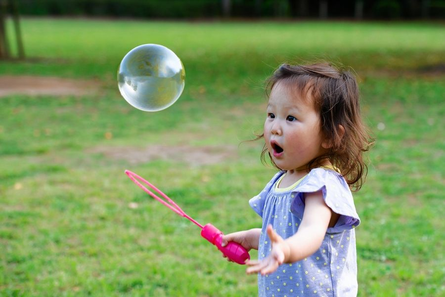 Quiet outdoor activities like playing with bubbles appeal to children with autism, as opposed to loud games like tag.