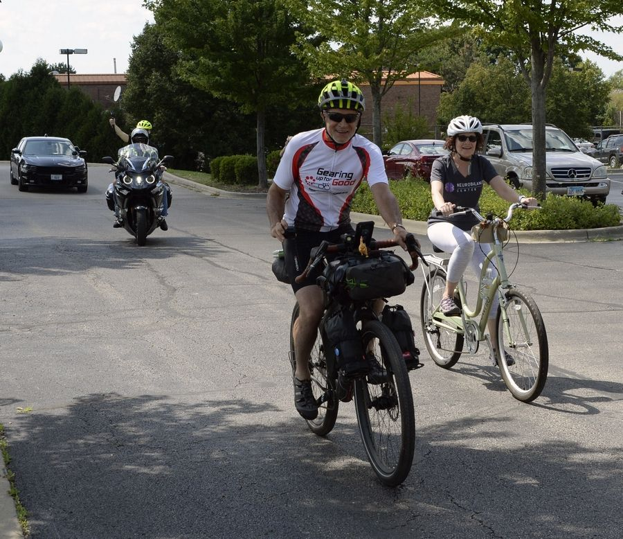 Cincinnati business executive Joe Motz, 65, rides into the NeuroBalance Center parking lot in Barrington on Wednesday with a police escort and the facility's co-founder, Joy Wagner of Inverness, by his side. He's on a 6,500-mile bicycle trip to raise $650,000 to help those with Parkinson's disease.