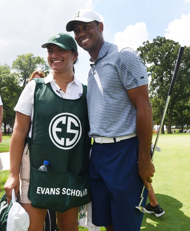 Evans Scholar Sarahi Ortiz has her photo taken with Tiger Woods after she caddied for the 15-time major champion during his pro-am round Wednesday at Medinah.