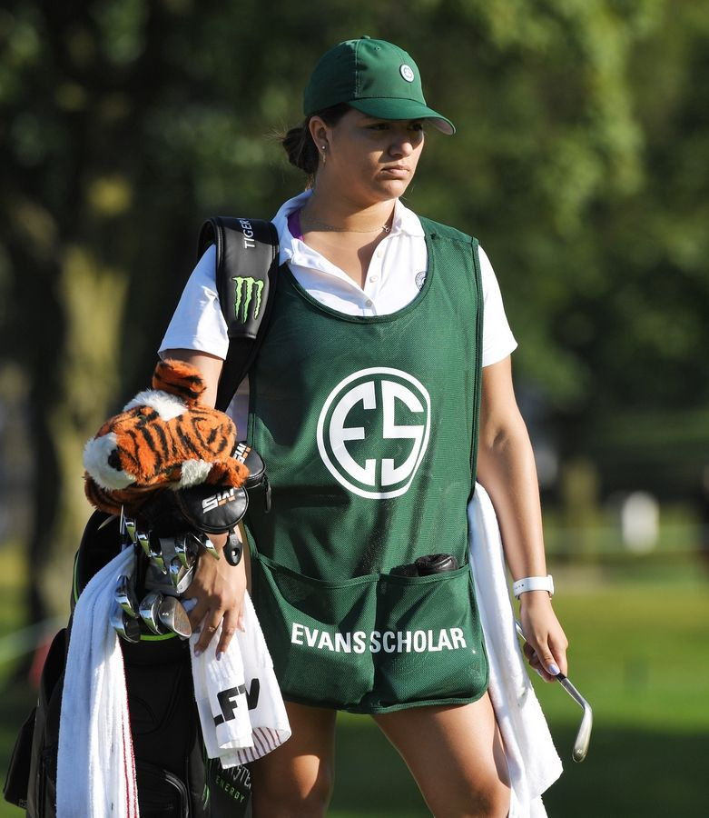 Evans Scholar Sarahi Ortiz serves as Tiger Woods' caddie during the BMW Championship pro-am at Medinah Wednesday.